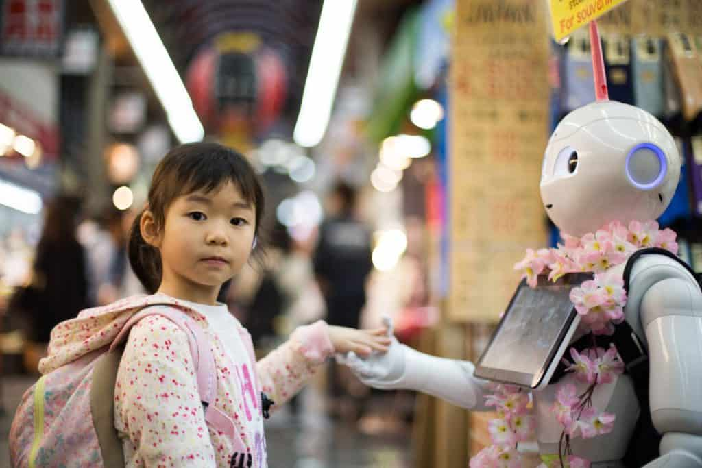 Young Asian girl holding hands with a robot.
