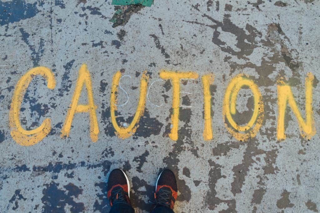 Birdseye view of someone standing on road with 'caution' written in yellow paint.